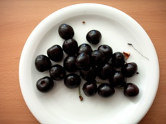 Schwarze Kirschen auf einem weißen Teller