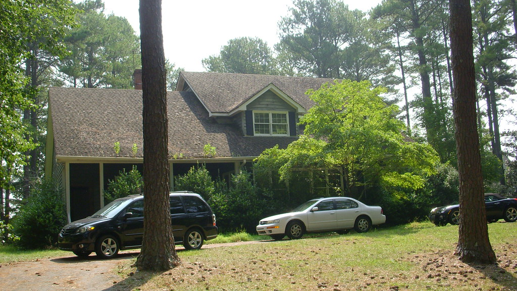 House from driveway/two large pines