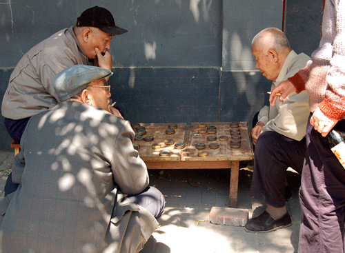 Old men stooping at a gameboard