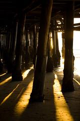 Under the Pier (Hal Bergman Photography) Tags: ocean california ca light sunset sunlight beach vertical evening la pier losangeles saturated sand moody santamonica piers highcontrast nobody landmark pacificocean photograph daytime santamonicapier pillars famousplace willrogersstatebeach
