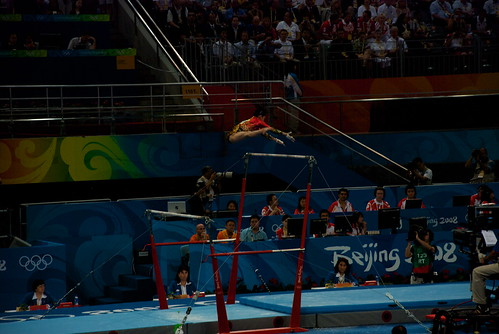 A Chinese gymnast goes airborne between the parallel bars.