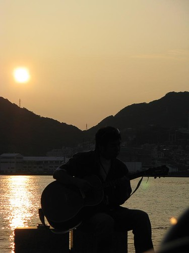 guy playing guitar on the pier