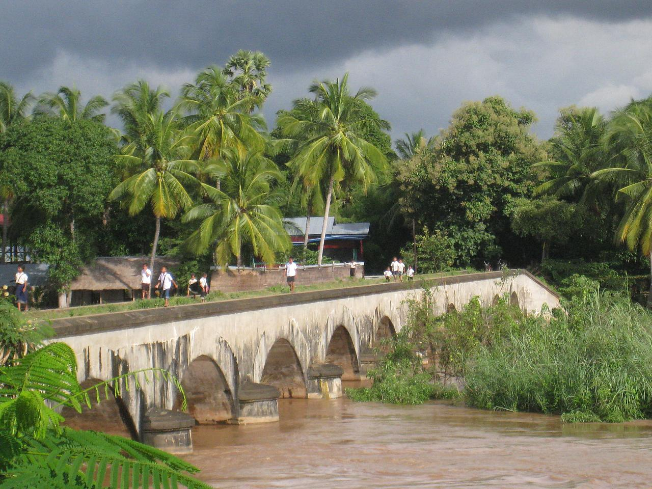 School kids cross the an old bridge built by the French to connect Don Det and Don Khone (islands).