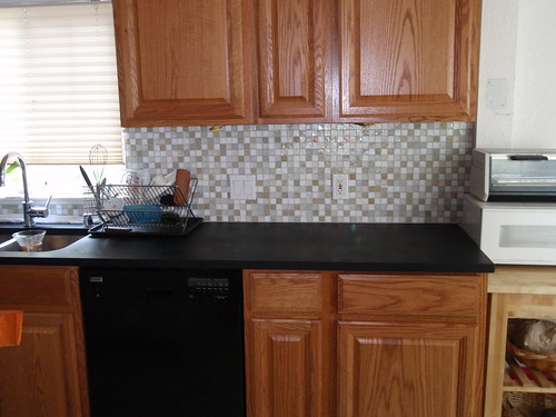 Granite countertops and stainless steel appliances recycled glass tile (creme brulee)