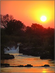 Sunset over Popofalls, Botswana (JenvanW) Tags: trees sunset red orange water yellow waterfall rocks botswana fiatlux zambeziriver golddragon popofalls