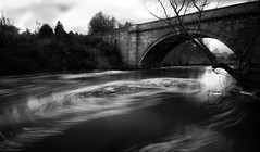 swirl (Ray Byrne) Tags: longexposure bridge blackandwhite bw castle water river monotone alnwick northumberland whirlpool terrorists swirl troubled lyricists riveraln raybyrne cysts denwicklanebridge bamalam iwilllaymedown jetplaneleavingon byrneoutcouk webnorthcouk