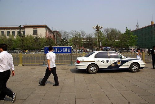 Tourists and police car on Tian'anmen Square
