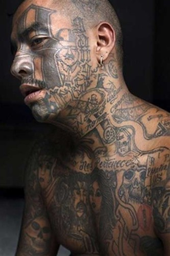 """Smoking"" with facial tattoos that reference the Mara gang"