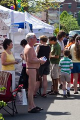 Man in loincloth (Culinary Fool) Tags: seattle man tents crowd canopy universitydistrict loincloth streetfair artsandcrafts pamphlets culinaryfool nearlynaked whatwashethinking udist avoidingeyecontact