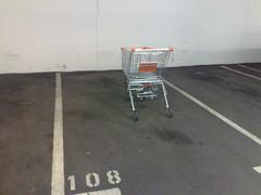 Geringer Benzinverbrauch - Einkaufswagen auf einem Autoabstellplatz stehend