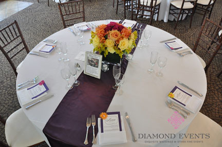 Table with Eggplant runner and colorful flower arrangement