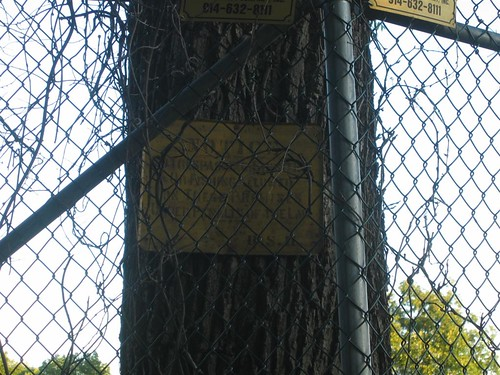 Old no trespassing sign behind fence