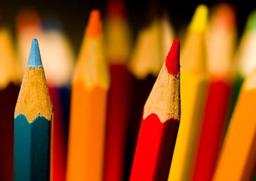Fotografía de un conjunto de lapices de colores afilados en los que están enfocados en azul claro y el rojo,el resto desenfocados