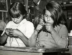 two girls knitting at a school desk