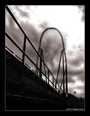 Fasten your seat belts (Pipall) Tags: uk england bw monochrome vertical clouds canon blackwhite ride ominous perspective fast drop surrey rails stealth amusementpark themepark pointshoot staines thorpepark dodgeburn ixus65