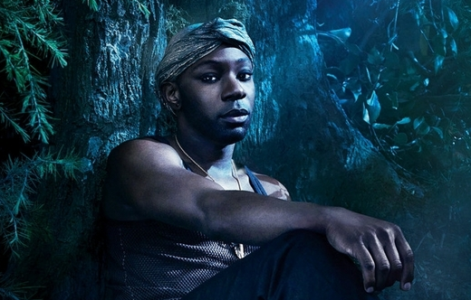 Lafayette Reynolds, a young black man, sits against a tree and looks at the camera. He's wearing a tank top and a headscarf
