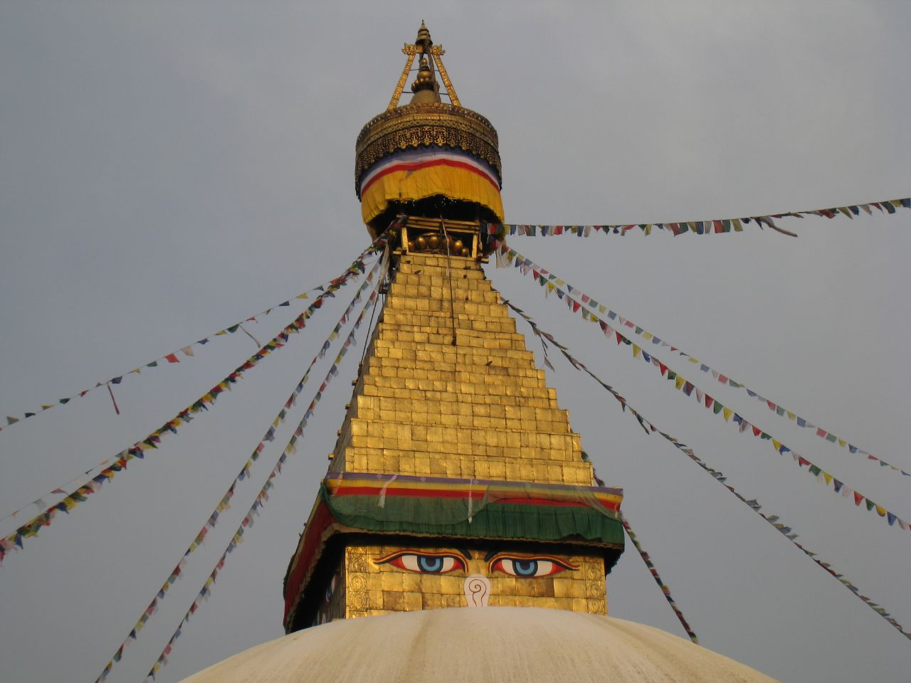 The top of the stupa glows golden at sunset