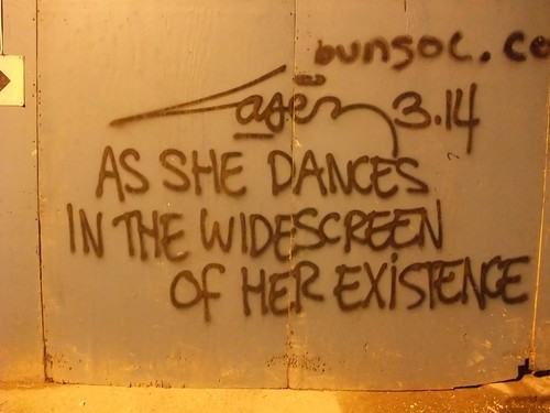 "London graffiti-- text: ""as she dances in the widescreen of her existence"""