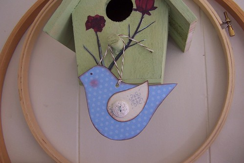 Little birdie hanging on a birdhouse