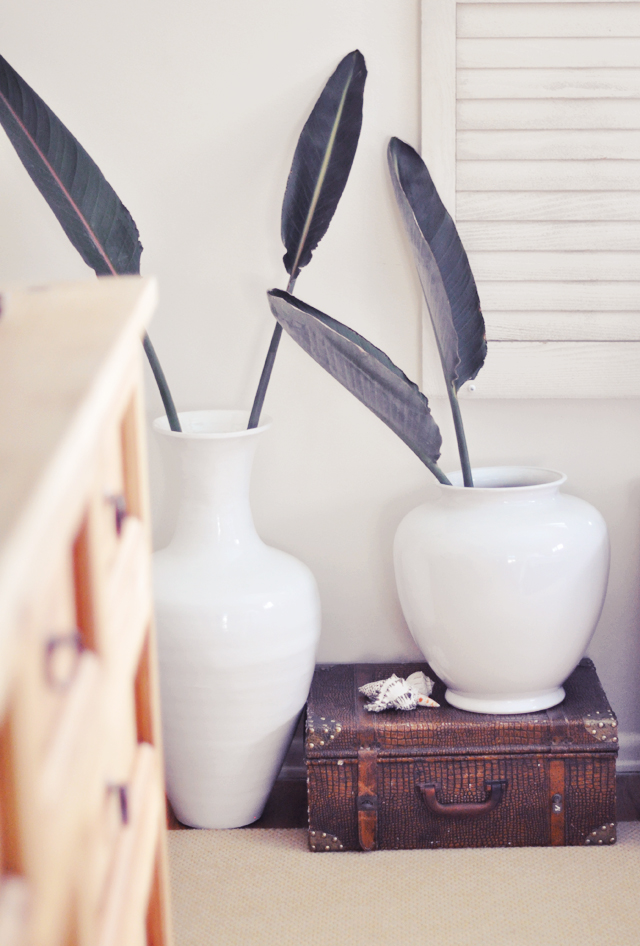 big white vases in  the  master bedroom  + vintage suitcase and shells