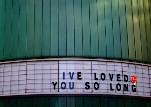 Fotografía de la fachada de un cine o similar con un letrero que reza I've Loved You So Long