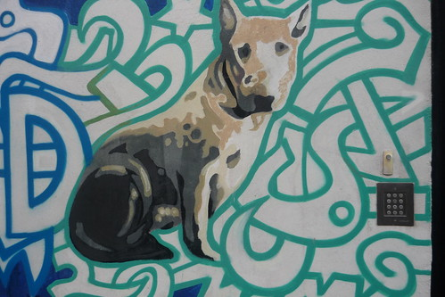 graffiti of a pit bull terrier sitting in the midst of blue and green line drawings