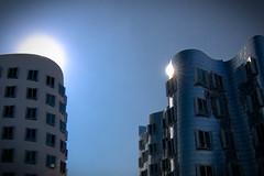 Sunrise over Gehry buildings (tmg83) Tags: blue bw building clouds sunrise canon germany deutschland media glow slim harbour wolken tokina1224 gehry nrw düsseldorf 77 medienhafen polfilter eos400d
