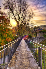 Small bridge (Tambako the Jaguar) Tags: bridge autumn trees sunset sky sun castle metal stone clouds switzerland nikon hill wideangle explore 12mm chteau hdr neuchtel chemin d300 photomatix mywinners impressedbeauty flickrlovers