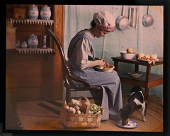 Genre scene, woman in kitchen peeling vegetables (George Eastman House) Tags: dog cooking kitchen cook apron jars jackrussellterrier georgeeastmanhouse headgear wickerchair williamsimon peelingapples photo:process=colorplatescreenautochromeprocess lickingplate color:rgb_avg=5d453c drwsimon drwilliamsimon geh:accession=198300630001