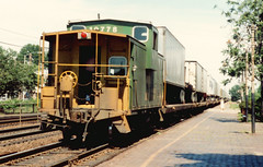 Eastbound Burlington Northern freight train with a caboose. Berwyn Illinois. July 1985.