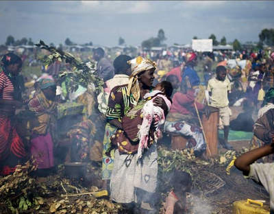 A group of Congolese displaced cook as they stay in an improvised camp in Kibati