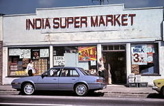 gm_16612 India Super Market, Vancouver, Main Street in 1984 (CanadaGood) Tags: blue white canada color colour building car sign vancouver analog shopping store automobile mainstreet bc pavement britishcolumbia parking slidefilm best 1984 vehicle streetphoto kodachrome grocerystore agriculture eighties favourite canadagood slidecube