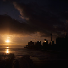 Say Goodbye .. (Js) Tags: city bridge winter light sunset sky sun lake toronto reflection 6x6 film ice silhouette clouds mediumformat dark square landscape frozen glow cityscape shadows cloudy kodak horizon freezing slide transparency positive icy lakeontario ektachrome e200 yashica innerharbour cherrystreet mat124g