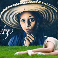 The lady from Saigon (Sator Arepo) Tags: park eye grass wall reflex mural grafitti olympus vietnam resting curiosity saigon zuiko nam mitjana lerida e500 uro 50200mmed parcdelamitjana gettyimagesiberiaq3