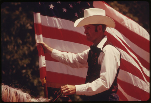 Rider with an American Flag on Horseback in a Parade on the Main Street of Cottonwood Falls, Kansas, near Emporia...06/1974