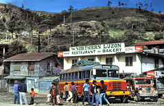 gm_01941 New Northern Luzon Bakery, Bontoc Philippines 1985 (CanadaGood) Tags: philippines luzon banaue analog bakery truck jeepney 1985 cocacola slidefilm kodachrome restaurant slidecube red blue yellow colour color white bus building person people asia canadagood mountain sign vehicle streetphoto text