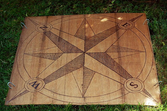 Old fashioned style fixed compass, burned into a sheet of plywood