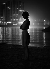 In the still of the night (noamgalai) Tags: ocean sea portrait blackandwhite bw woman beach girl standing photo sand dress picture photograph backlit    noamg noamgalai