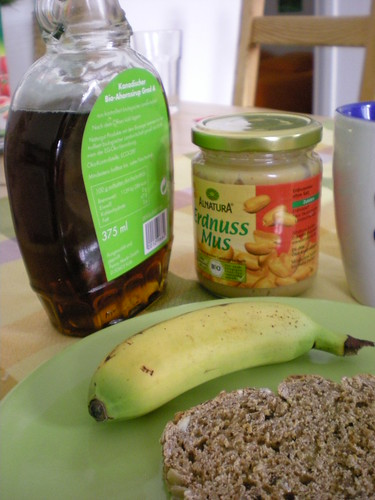 tostada, mini-plátano, mantequilla de cacahuete, jarabe de arce y té con leche