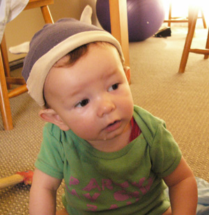 Small, drooly baby wearing a viking-style horned hat made form soft materials, in navy and cream.