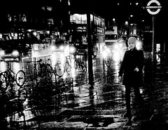Raintown (Ian Brumpton) Tags: street uk england blackandwhite bw london rain night underground shower blackwhite noir britain pavement streetphotography headlights bicycles explore sidewalk londres angleterre showers londonbus streetphotographer womaninblack explored flickrsbest girlinblack blackwhitephotos platinumphoto infinestyle newacademy alwaysexc novavitanewlife artistictreasurechest musicsbest
