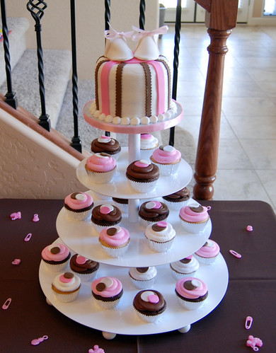pink and brown baby shower cupcake tower with baby booties topper
