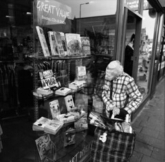(Dr Karanka) Tags: uk blackandwhite woman reflection wales mediumformat fuji cardiff books squareformat teddybear oldlady mamiya6 neopan400 rodinal albanyroad roath checks whitehair lowfat darktide greatvalue lookingatwindow
