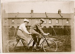 Bicycle built for two (version two) (Mike Gerrish) Tags: hat fashion bike sepia blackwhite dress moustache cycle tandem 1910s foundphoto touring edwardian 1920 tweed stylish bsa 3speed flatcap foundimage threespeed saddlebag terracedhouses plusfours backyardportrait holidaypicturesalbum acetylenelamps resilioncantileverbrakes