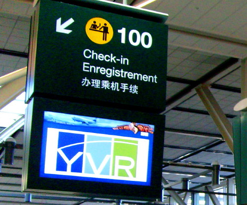 Check-in sign at YVR with English, French and Chinese language