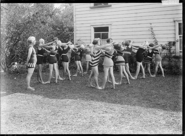 Group of girls practicing a life-saving technique. ca 1910s