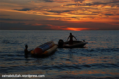 Two banana ride operators were towing their banana ride preparing to go home in Teluk Kemang Beach in Port Dickson