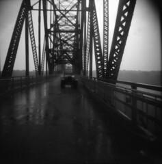 (Hilary (curioush)) Tags: bridge bw film car holga route66 stlouis mississippiriver chainofrocksbridge ilforddelta steeltrusses