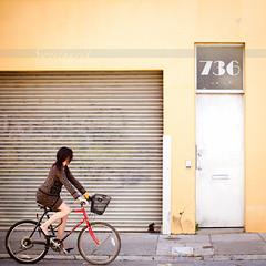 25 :: 31 (sweethardt) Tags: door woman building bike bicycle yellow metal female garage skirt suit sidewalk jacket corrugated transom 736