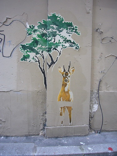 graffiti, wheat pasted maybe, of a young male deer beneath a green tree